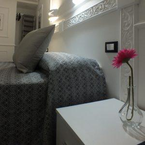camera rome central inn comodino su cui c'è un fiore rosa