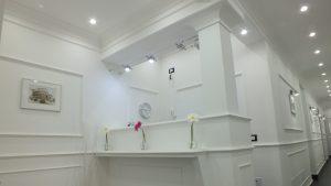 reception rome central inn bianca con fiori colorati e quadri di monumenti
